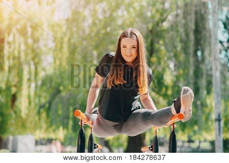 Fitness girl walks in the park and engaged in various exercises with weights and mat