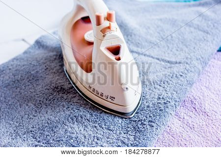 laundry set with colorful towels and iron on fabric background