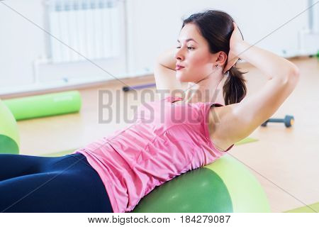 Fit women doing sit-ups on exercise balls