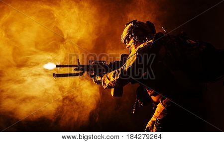 Security forces operator in Combat Uniforms with machine gun, shooting in the face of danger. Facing enemy, he is ready to protect the nation. Gun blazing. Studio contour silhouette shot, backlight, profile side view