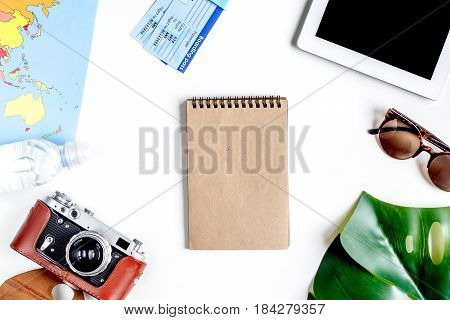 vacation concept with traveller outfit map, camera, copybook on white desk background top view