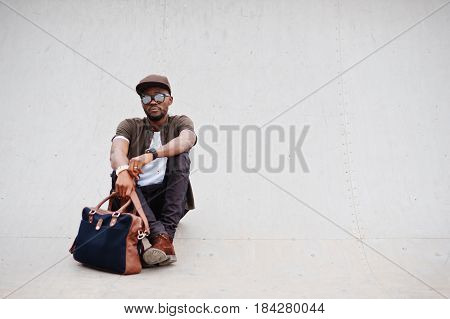 Portrait Of Sitting Stylish African American Man Wear On Sunglasses And Cap With Handbag Outdoor. St