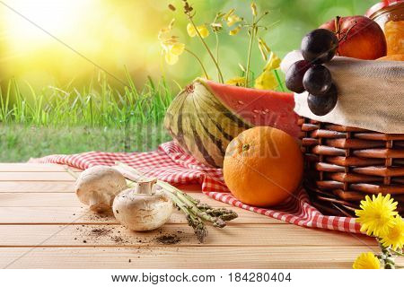 Picnic Wicker Basket With Food On Table In Field Closeup