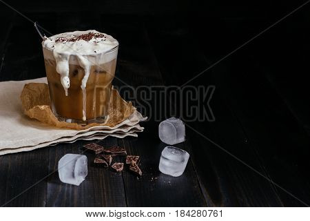 Ice Coffee Drink With Chocolate And Ice Cubes On The Wooden Table, With Copy Space