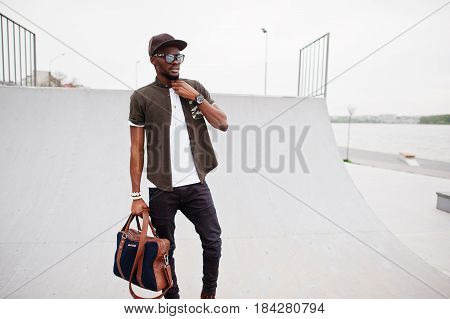 Portrait Of Sitting Stylish African American Man Wear On Sunglasses And Cap With Handbag Outdoor Aga