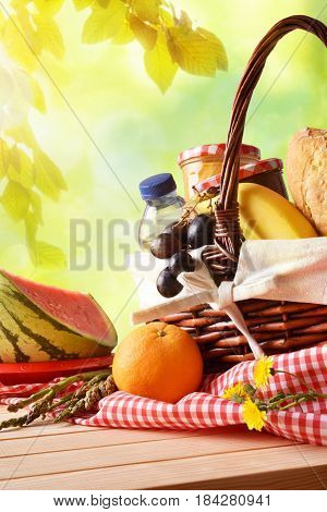 Picnic Wicker Basket With Food On Table In Field Vertical