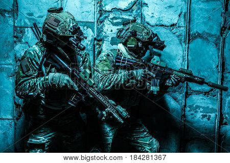 Squad of Army Rangers moving along the concrete wall on mission. They are ready to contact with enemy and to kill. Outdoor location shot, darkness of night, dim light