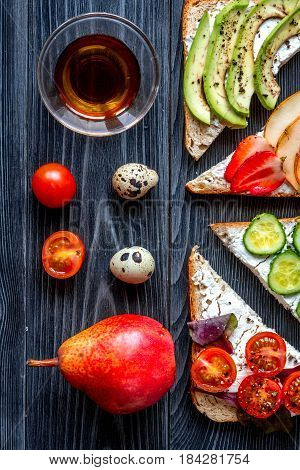 lunch with triangle sandwiches with fruits and vegetables on dark table background top view