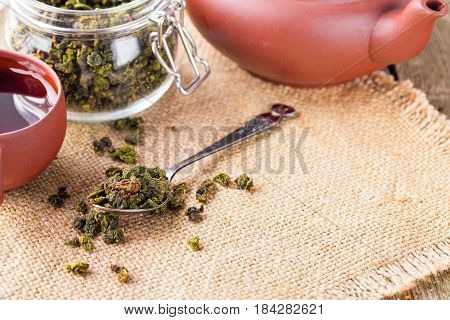 Dry leaves of green tea in a glass jar. Nearby tea leaves in a teaspoon and ceramic tea-things. Composition on a napkin from a sacking. The cover banks is open several tea leaves are scattered. Light background