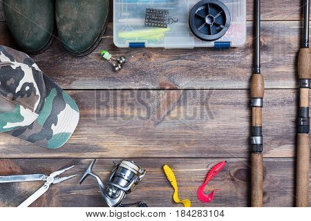 Fishing rods and reel with boots cap and fishing tackles in a box on wooden background with free space.