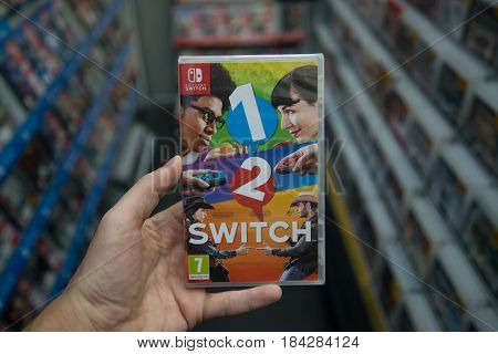 Bratislava, Slovakia, circa april 2017: Man holding 1-2-Switch videogame on Nintendo Switch console in store