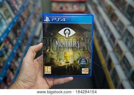 Bratislava, Slovakia, circa april 2017: Man holding Little nightmares videogame on Playstation 4 console in store