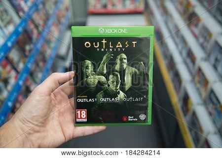 Bratislava, Slovakia, circa april 2017: Man holding Outlast trinity videogame on Microsoft XBOX One console in store