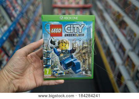 Bratislava, Slovakia, circa april 2017: Man holding Lego city undercover videogame on Microsoft XBOX One console in store