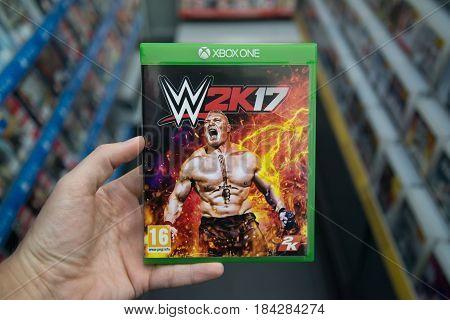 Bratislava, Slovakia, circa april 2017: Man holding WWE 2K17 videogame on Microsoft XBOX One console in store