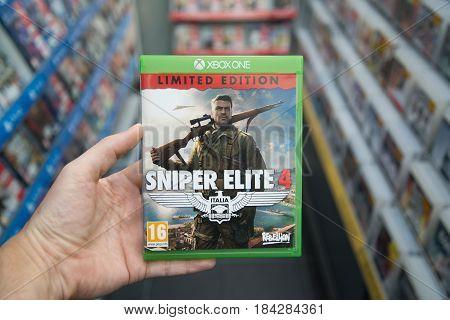 Bratislava, Slovakia, circa april 2017: Man holding Sniper Elite 4 videogame on Microsoft XBOX One console in store