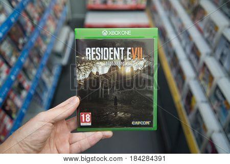 Bratislava, Slovakia, circa april 2017: Man holding Resident evil 7 videogame on Microsoft XBOX One console in store