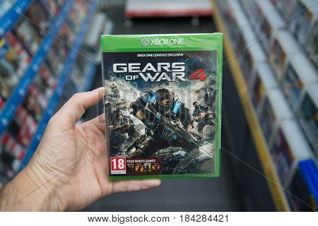 Bratislava, Slovakia, circa april 2017: Man holding Gears of War 4 videogame on Microsoft XBOX One console in store