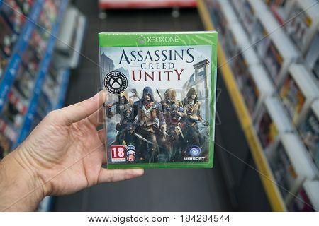 Bratislava, Slovakia, circa april 2017: Man holding Assassin's Creed Unity videogame on Microsoft XBOX One console in store