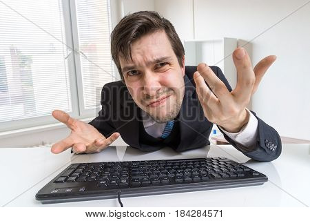 Confused And Unsure Man Is Working With Computer.