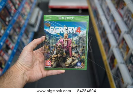 Bratislava, Slovakia, circa april 2017: Man holding Far Cry 4 videogame on Microsoft XBOX One console in store