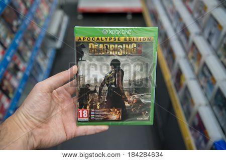 Bratislava, Slovakia, circa april 2017: Man holding Dead Rising 3 videogame on Microsoft XBOX One console in store