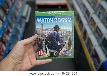 Bratislava, Slovakia, circa april 2017: Man holding Watch Dogs 2 videogame on Microsoft XBOX One console in store