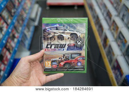 Bratislava, Slovakia, circa april 2017: Man holding The crew ultimate edition videogame on Microsoft XBOX One console in store