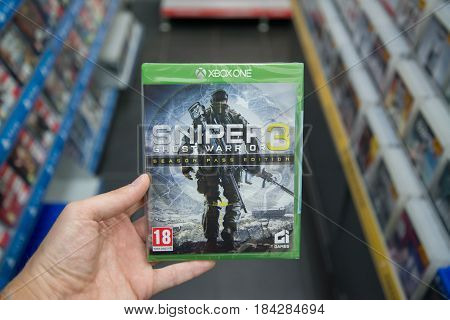 Bratislava, Slovakia, circa april 2017: Man holding Sniper Ghost Warrior 3 videogame on Microsoft XBOX One console in store