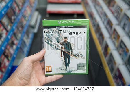 Bratislava, Slovakia, circa april 2017: Man holding Quantum break videogame on Microsoft XBOX One console in store
