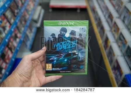 Bratislava, Slovakia, circa april 2017: Man holding Need for Speed videogame on Microsoft XBOX One console in store