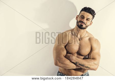 Muscular bodybuilder leaning against white wall, looking at camera, with large copyspace next to him