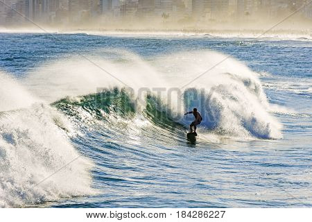 Surfer and wave with water spray at Ipanema beach in Rio de Janeiro
