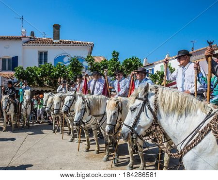 Sent-Mari-de-la-Mer, Provence, France - May 25, 2015. The concept of ethnographic and active tourism. Security guards on  white horses expect the beginning of a parade of the World festival of Gypsies