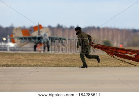 KUBINKA, MOSCOW REGION, RUSSIA - APRIL 24, 2017: Soldier picks up dropped parachute of Sukhoi Su-25 airplane of Russian air force during Victory Day parade rehearsal at Kubinka air force base.