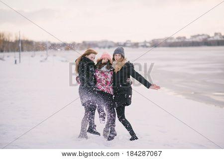 three girls walking on the frozen river