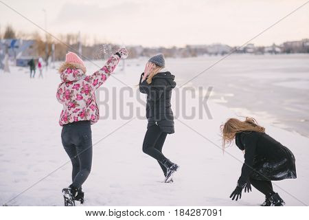 three girls walking on the frozen river