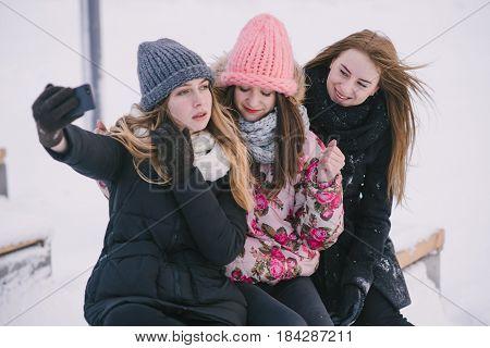 three girls sittin on the frozen river