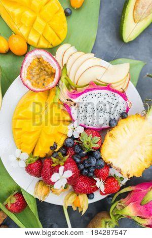 Exotic fruits. Summer photo concept. Mango. A pineapple. Avocado. Kiwi. Pitahaya.. Kumhvat. Copyspase. Fresh fruits. Exotic fruits on a gray background. Blueberry. Strawberry. Physalis. Tamarind