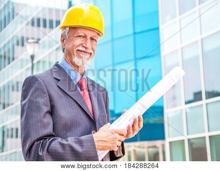 an Happy smiling older architect looking out