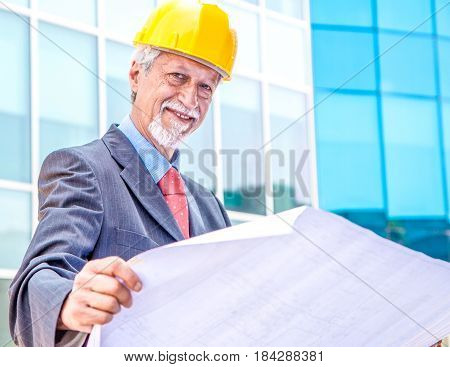 a senior Architect Looking At Blueprint outdoor