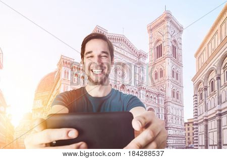 Young tourist taking selfie in front of Florence Cathedral Santa Maria del Fiore at sunrise, Tuscany, Italy