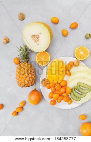 Exotic fruit still life of pineapple, mango, granadilla, kumquat, fizalis, melon, and oranges on a gray background.