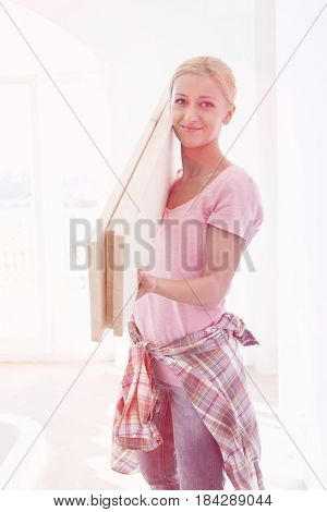 Portrait of beautiful woman carrying wooden planks on shoulder