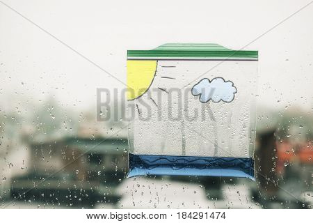 water cycle in a bag. a  plastic bag with water and painted on it with a cloud and the sun hanging in the window. clouds form and rain fall in the bag. science experiment for children poster