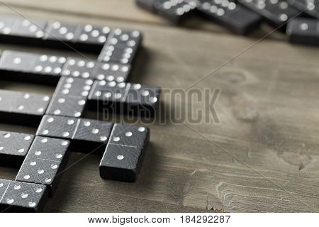 Game of domino with domino stones on wooden background; selective focus on domino stone in front