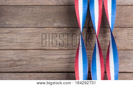 Red white and blue ribbons on a wood background