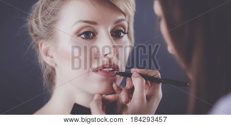 Artist doing professional make up of woman.