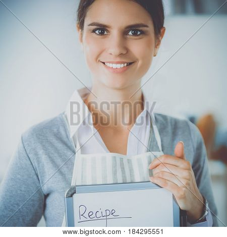Woman in the kitchen at home standing with recipe.