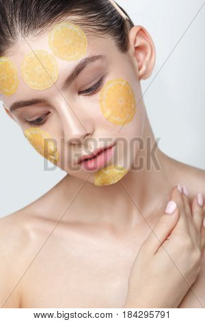 Beautiful young cheerful woman with refreshing mask on her face isolated on white background, looking down